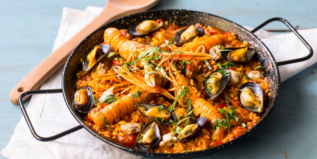 Paella is a rice dish from Spain with the a combination of seafood such as shrimp, oysters and squid or fish with white rice and a variety of herbs.
